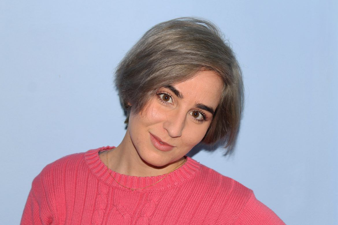 Close up of Saida with grey hair and a pink sweater over a light blue backdrop